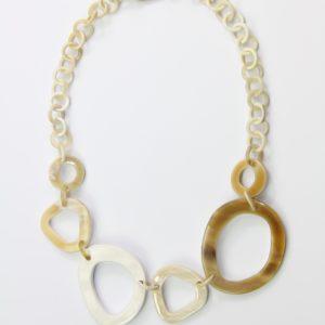 Collier en corne beige-blanc avec 1 élément laqué blanc. Eléments du centre environ 4 à 5 cm, éléments de la « chaîne » environ 12 mm de diamètre. Longueur ajustable jusqu'à 49 cm. Orligne Genève LQP12 SOY-1-1